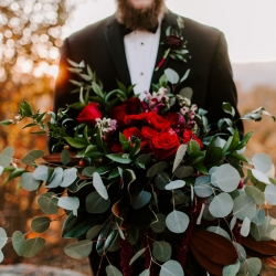 Stunning bouquet by Magnificent Moments Weddings features dark burgundy roses among stunning greenery accents