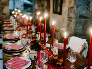 Folk and Wayfarer Photography captures farmhouse reception tables lined with burgundy tapered candles and elegant glassware all designed by Magnificent Moments Weddings