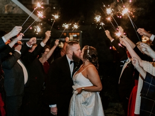 Bride and groom kiss under sparklers as they leave their fall wedding at Jump Off Rock coordinated by Magnificent Moments Weddings
