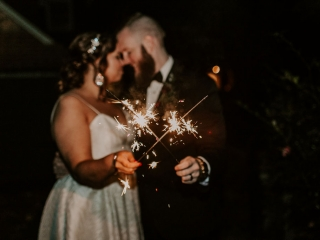 Bride and groom show off sparklers before their grand exit at their fall wedding at Jump Off Rock in Asheville, North Carolina