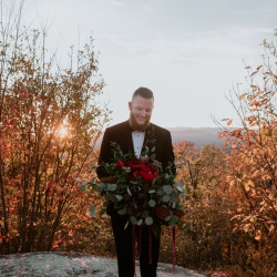 Groom holds a stunning bridal bouquet designed by Magnificent Moments Weddings for their fall wedding at Jump Off Rock