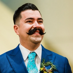 Gandee Photography captures a smiling groom as he waits for his bride to walk down the aisle during their wedding ceremony at St Gabriel's Catholic Church