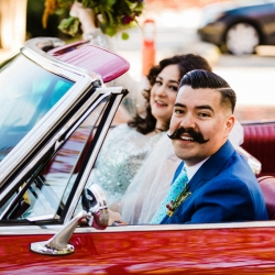 Bride and groom pose in a vintage convertible during their fall wedding at Catawba Brewery