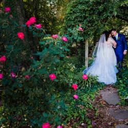 Bride and groom pose in a lush garden after their wedding ceremony at St Gabriel's Catholic Church