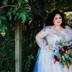 Bride poses for Gandee Photography holding a stunning bright floral bouquet created by Willow Floral Boutique
