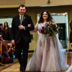 Bride walks down the aisle holding a colorful bridal bouquet created by Willow Floral Boutique