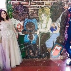 Bride and groom pose among fun art murals during their fall wedding coordinated by Magnificent Moments Weddings
