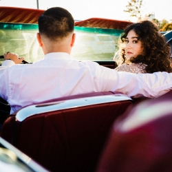 Bride looks back at Gandee Photography as she rides off with her new groom in a vintage convertible