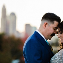 Bride and groom share a sweet moment in front of the Charlotte skyline during their fall wedding coordinated by Magnificent Moments Weddings