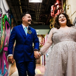 Bride and groom post among colorful graffiti during their wedding at Catawba Brewery