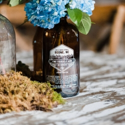 Old beer bottles make the perfect vases for colorful flowers during at wedding at Catawba Brewery