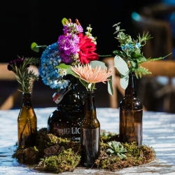 Unique centerpieces of beer bottles feature stunning colorful flowers by Willow Floral Boutique