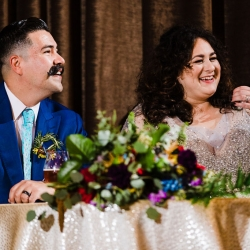 Bride and groom enjoy toasts from family and friends during their wedding reception coordinated by Magnificent Moments Weddings