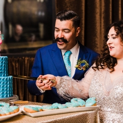 Bride and groom cut their striking teal cake created by Suarez Bakery