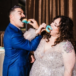 Bride and groom share a sweet treat of donuts created by Suarez Bakery during their reception coordinated by Magnificent Moments Weddings