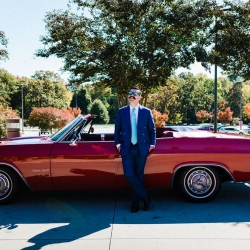 Gandee Photography captures a groom posing in front of vintage convertible
