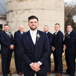 Groom poses with his groomsmen among the grounds of The Diary Barn