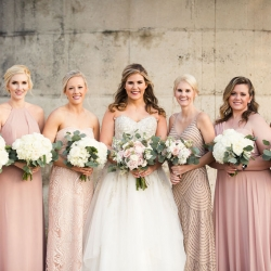 Bride poses with her bridesmaids all wearing blush pink dresses and holding stunning bouquets created by Buy the Bunch