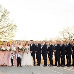 Bride and groom pose with their bridal party among the grounds of The Diary Barn