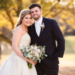 Bride and grooms smile for Grace Hill Photography during their fall wedding