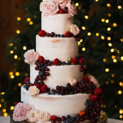 Four tiered cake by Nona's Bake featured fresh fruit and flowers for a winter wedding at The Diary Barn