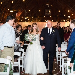 Bride is escorted down the aisle by her father during her winter wedding at The Diary Barn