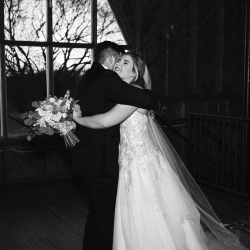 Bride and groom share a hug during their fall wedding reception at The Diary Barn