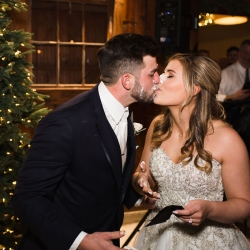 Bride and groom share a kiss after cutting their cake during a reception coordinated by Magnificent Moments Weddings