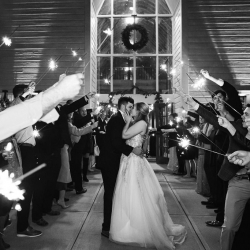 Bride and groom share one last kiss during their sparkler send off coordinated by Magnificent Moments Weddings