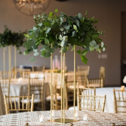 Spring Vine Design created stunning greenery centerpieces raised on gold stands