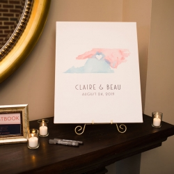 Water color canvas guestbook shows off bride and grooms home states for a summer wedding reception at Terrace at Cedar Hill