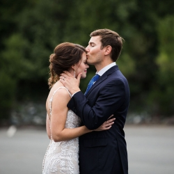 Groom kisses his bride as they share a sweet moment during their summer wedding in Uptown Charlotte