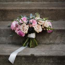 Stunning bridal bouquet created by Spingvine Design featured blush and pink roses tied with a simple white ribbon