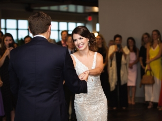 Bride smiles during her first dance with her groom during her summer wedding in Uptown Charlotte captured by Grace Hill Photography