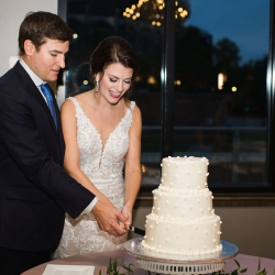 Bride and groom cut their three tiered white cake from Publix during their summer wedding reception coordinated by Magnificent Moments Weddings