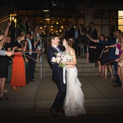 Bride and groom exit their wedding reception at Terrace at Cedar Hill through a sea of glow sticks and cheering friends
