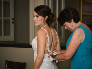 Brides mother puts the finishing touches on her dress during her summer wedding at Bonterra Wine Room