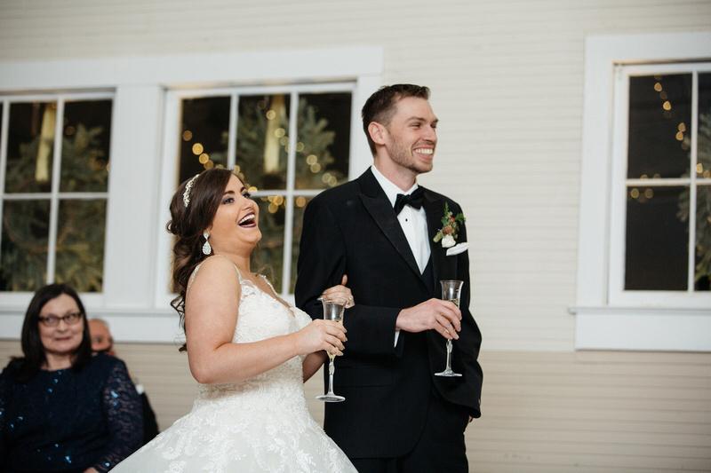 Bride and groom enjoy toasts at their Dairy Barn Wedding