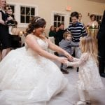 Bride dancing with young guest at a Diary Barn Wedding