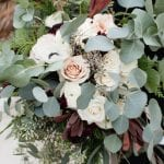 Stunning bridal bouquet full of greenery and muted red accents created by Buy the Bunch