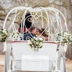 Bride and groom pose in fairy tale carriage from Southern Breezes