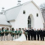 Bride and groom pose in front of The Dairy Barn before their wedding coordinated by Magnificent Moments Weddings