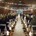 Grain and Compass captures stunning picture of candle lined aisle at a Diary Barn wedding