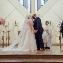 Green Valley Photography captures a bride and groom exchanging a kiss during their wedding ceremony at St Gabriel's Catholic Church