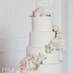 Celestial Cakes created a stunning four tier cake draped in flowers and topped with the couples initials all captured by Green Valley Photography