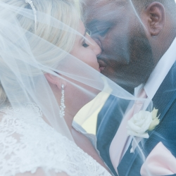 Green Valley Photography captures a kiss under the brides veil during a spring wedding in Charlotte, North Carolina.