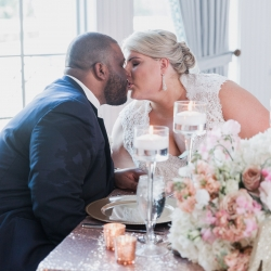 Bride and groom share a sweet kiss over dinner created by Providence Country Club for their spring wedding coordinated by Magnificent Moments Weddings