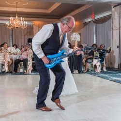 Brides father rocks out on a fake guitar during a cute father daughter dance coordinated by Magnificent Moments Weddings