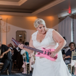 Bride rocks out with a blow up guitar during a fun father daughter dance during her wedding reception at Providence Country Club
