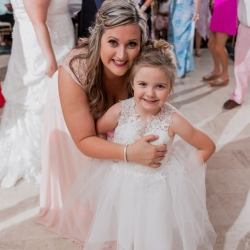 Flower girl poses with a bridesmaid for Green Valley Photography during a spring wedding at Providence Country Club